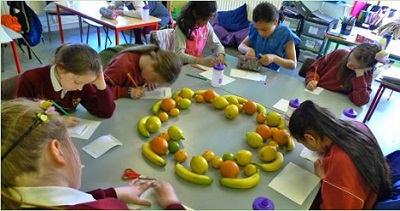 Pupils in the classroom drawing fruit, as part of 'Coastlines, Maps and Melons', Martina Galvin's visual art project 2017/18